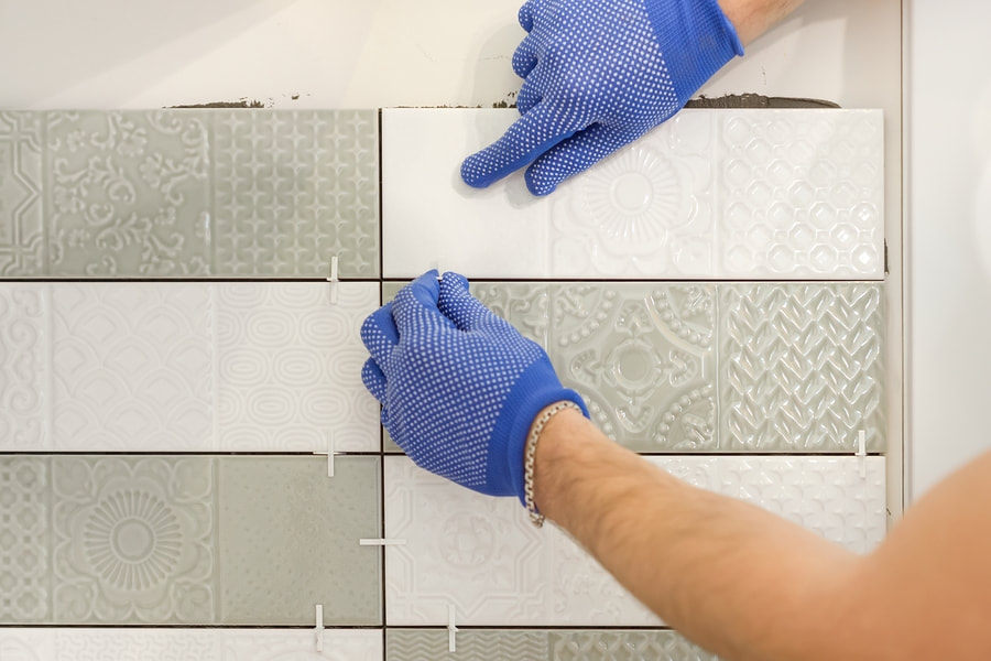 professional tiler working on wall tiling